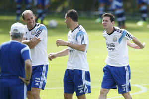 Photo - Argentina's Lionel Messi, right, warms up next to teammates Argentina's Maxi Rodriguez, center, and Argentina's Pablo Zabaleta during a training session in Vespasiano, near Belo Horizonte, Brazil, Wednesday, June 18, 2014.  Argentina plays in group F of the 2014 soccer World Cup. (AP Photo/Victor R. Caivano)