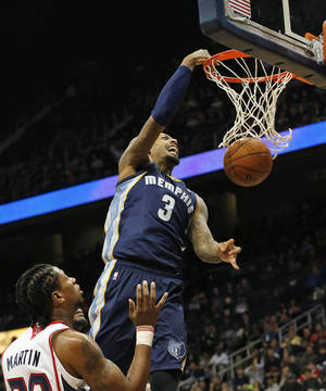 Photo - Memphis Grizzlies forward James Johnson (3) dunks as Atlanta Hawks forward Cartier Martin (20) defends during the second half of an NBA basketball game Saturday, Feb. 8, 2014, in Atlanta.  Memphis won 79-76. (AP Photo/John Bazemore)