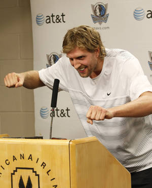Photo -   Dallas Mavericks' Dirk Nowitzki of Germany, jokingly demonstrates the workout he is using while recuperating from knee surgery while speaking to reporters at the American Airlines Center Tuesday, Oct. 23, 2012, in Dallas. Nowitzki meet with reporters for the first time since arthroscopic surgery on his right knee that's supposed to sideline him for six weeks. (AP Photo/LM Otero)