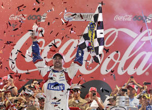 Photo - Jimmie Johnson celebrates in Victory Lane after winning the NASCAR Sprint Cup series Coca-Cola 600 auto race at Charlotte Motor Speedway in Concord, N.C., Sunday, May 25, 2014. (AP Photo/Chuck Burton)