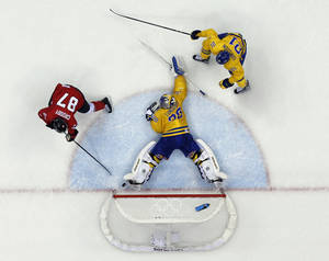 Photo - Canada forward Sidney Crosby scores a goal on Sweden goaltender Henrik Lundqvist during the second period of the men's gold medal ice hockey game at the 2014 Winter Olympics, Sunday, Feb. 23, 2014, in Sochi, Russia. (AP Photo/David J. Phillip )