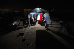 Photo - People take shelter under a tent decorated with a Chilean flag after evacuating their homes due to earthquakes in Alto Hospicio, Chile, Thursday, April 3, 2014. Coastal residents of Chile's far north spent a second sleepless night outside their homes as major aftershocks continued Thursday following a magnitude-8.2 earthquake that damaged several thousand homes and caused six deaths. (AP Photo/Luis Hidalgo)
