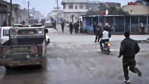 photo - This Sunday, Dec. 23, 2012 image taken from video obtained from the Shaam News Network, which has been authenticated based on its contents and other AP reporting, shows Free Syrian Army fighters running towards the scene after a government airstrike hit Hama Suburb of Halfaya, Syria. A government airstrike Sunday on a bakery in a rebel-held town in central Syria killed tens of people, which left scattered bodies and debris up and down a street, and more than a dozen wounded were trapped in tangled heap of dirt and rubble, activists said. (AP Photo/Shaam News Network via AP video)