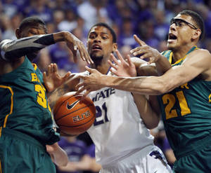 Photo - Kansas State forward Jordan Henriquez (21) tries to get a rebound between Baylor forward Cory Jefferson (34) and center Isaiah Austin (21) during the first half of an NCAA college basketball game in Manhattan, Kan., Saturday, Feb. 16, 2013. (AP Photo/Orlin Wagner)