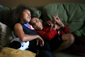 Photo - Tobias, 11, at left, and his brother Titus, 12, sit on a sofa inside their Edmond, Okla., home on Thursday, Jan., 9, 2014. Titus has cerebral palsy and other medical issues which prevent him from walking. He is able to run races with his brother Tobias who pushes him in a stroller. Photo by Bryan Terry, The Oklahoman <strong>Bryan Terry - THE OKLAHOMAN</strong>