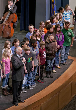 Photo - Richard Zielinski, conductor of the new Norman Philharmonic, introduces the Norman School District's fifth-grade honor choir in a performance of an anthem written especially for Norman by composer Libby Larsen. PHOTO BY STEVE SISNEY, THE OKLAHOMAN <strong>STEVE SISNEY</strong>