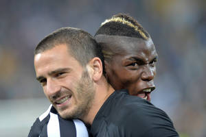 Photo - Juventus players Paul Pogba, right, and Leonardo Bonucci, left, celebrate at the end of a Serie A soccer match againsts Atalanta, at the Juventus stadium, in Turin, Italy, Monday, May 6, 2014. Juventus clinched its third straight and 30th overall Serie A title. (AP Photo/Massimo Pinca)