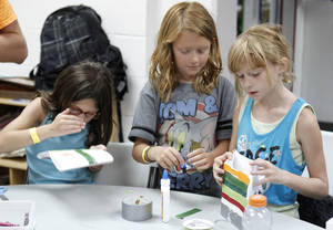 Photo - Seven-year-olds Audrey Hill, left, Claire Gibson and Sydney Jones work together to make peace lanterns at the Edmond YMCA in observance of the upcoming anniversary of the Hiroshima bombing.  Photo By Paul Hellstern, The Oklahoman