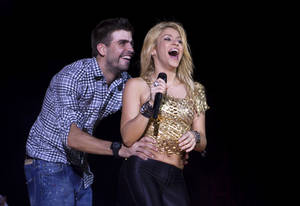 "Photo -   FILE - This May 29, 2011 file photo shows Colombia's singer Shakira performs with FC Barcelona Gerard Pique during The Sun Comes Out World Tour concert in Barcelona, Spain. Shakira is pregnant with her first child. The 35-year-old posted on her website Wednesday that she and boyfriend Gerard Pique ""are very happy awaiting the arrival of our first baby."" Pique, who is from Barcelona, is a soccer player for FC Barcelona. (AP Photo/Emilio Morenatti, file)"