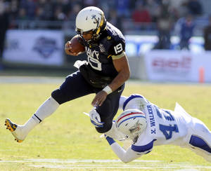 Photo - Navy Midshipmen quarterback Keenan Reynolds (19) runs through a tackle attempt by Middle Tennessee Blue Raiders safety Xavier Walker (42) in the first half Armed Forces Bowl NCAA college football game, Monday, Dec. 30, 2013, in Fort Worth. (AP Photo/Matt Strasen)
