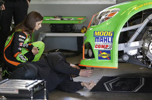 Photo - Driver Danica Patrick, left, watches as crew members make adjustments to her car during practice for the NASCAR Daytona 500 auto race at Daytona International Speedway in Daytona Beach, Fla., Saturday, Feb. 15, 2014. (AP Photo/John Raoux)