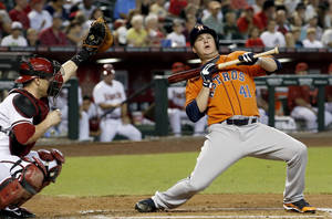 Photo - Houston Astros' Brad Peacock (41) back away from an inside pitch as Arizona Diamondbacks' Miguel Montero, left, makes the catch during the second inning of a baseball game on Tuesday, June 10, 2014, in Phoenix. (AP Photo/Ross D. Franklin)