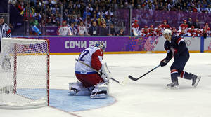 Photo - USA forward T.J. Oshie scores the winning goal against Russia goaltender Sergei Bobrovski in a shootout during overtime of a men's ice hockey game at the 2014 Winter Olympics, Saturday, Feb. 15, 2014, in Sochi, Russia. (AP Photo/Julio Cortez)