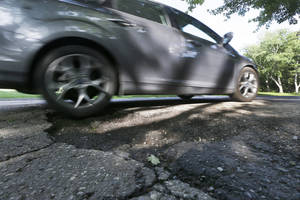 Photo - An automobile drives through a pothole in Bloomfield Township, Mich., Thursday, June 12, 2014. An effort to more than double Michigan's gasoline tax was defeated in the Republican-led state Senate, which left lawmakers scrambling to pass a scaled-back plan to improve deteriorating roads on their last day before adjourning for much of the summer. (AP Photo/Carlos Osorio)