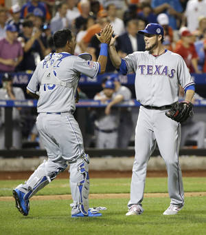 Photo - American League's Joe Nathan, right, of the Texas Rangers, is congratulated by American League's Salvador Perez, of the Kansas City Royals, after the final out in the ninth inning of the MLB All-Star baseball game, on Tuesday, July 16, 2013, in New York. The American League defeated the National League 3-0.(AP Photo/Matt Slocum)