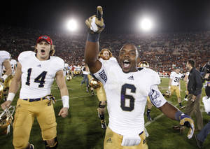 Photo -   Notre Dame running back Theo Riddick, right, and wide receiver Luke Massa, left, celebrate after Notre Dame defeated Southern California 22-13 in an NCAA college football game, Saturday, Nov. 24, 2012, in Los Angeles. (AP Photo/Danny Moloshok)