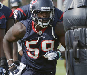 Photo -   Houston Texans' Whitney Mercilus eyes a tackling dummy during NFL football practice, Tuesday, June 12, 2012, in Houston. (AP Photo/Pat Sullivan)