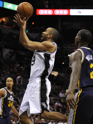 Photo - San Antonio Spurs guard Tony Parker, center, of France, shoots ahead of Utah Jazz forward Marvin Williams, right, as Jazz forward Richard Jefferson watches during the second half of an NBA basketball game, Wednesday, Jan. 15, 2014, in San Antonio. San Antonio won 109-105. (AP Photo/Darren Abate)