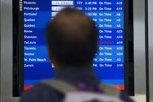 Photo - A traveler views a departures board Tuesday, July 22, 2014, at the Philadelphia International Airport in Philadelphia. The Federal Aviation Administration is telling U.S. airlines they are prohibited from flying to the Tel Aviv airport in Israel for 24 hours after a Hamas rocket exploded nearby. (AP Photo/Matt Rourke)