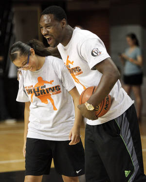 "Photo - FORMER OKLAHOMA STATE UNIVERSITY / OSU / COLLEGE BASKETBALL PLAYER / NBA BASKETBALL PLAYER / CHILD / CHILDREN / KIDS:  Former Oklahoma State basketball player and current Memphis Grizzlies player Tony Allen embraces Lizbeth Galvan, 14 of Oklahoma City, after she got a ball by him to make a layup at his ""Grit and Grind"" basketball camp at Gallagher-Iba Arena on July 31, 2013.  Photo by KT KING, The Oklahoman"