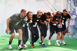 """Photo - German soccer players from left: Roman Weidenfeller, Shkodran Mustafi, Andre Schuerrle, Miroslav Klose, Mario Goetze and Toni Kroos celebrate on stage at the German team victory ceremony , near the Brandenburg Gate in Berlin,  Tuesday July 15,  2014.  Germany's World Cup winners shared their fourth title with hundreds of thousands of fans by parading the trophy through cheering throngs to celebrate at the Brandenburg Gate on Tuesday. An estimated 400,000 people packed the """"fan mile"""" in front of the Berlin landmark to welcome home coach Joachim Loew's team and the trophy — which returned to Germany for the first time in 24 years. (AP Photo/ Alex Grimm,Pool)"""
