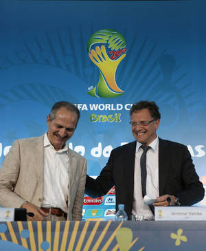 Photo - FIFA Secretary General Jerome Valcke, right, shares a light moment with Brazil's Sports Minister Aldo Rebelo after a local organizing committee 'LOC' Board Meeting press conference in Rio de Janeiro, Brazil, Friday, April 25, 2014. Valcke is visiting the World Cup host cities in Brazil, which is holding the 2014 soccer tournament. (AP Photo/Hassan Ammar)