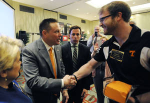 Photo - University of Tennessee head football coach Butch Jones is greeted by Daniel Williams after speaking at a legislative planning session sponsored by The Associated Press and the Tennessee Press Association on Thursday, Feb. 6, 2014, in Nashville, Tenn. Jones was the recipient of the Tennessee Press association Headliner of the Year Award. (AP Photo/Mark Zaleski)