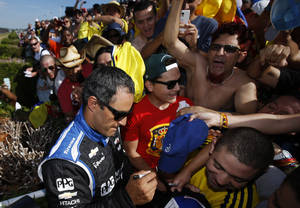 Photo - Juan Pablo Montoya, of Colombia, signs autographs for fans in the grandstand after he won the Pocono IndyCar 500 auto race, Sunday, July 6, 2014, in Long Pond, Pa. (AP Photo/Matt Slocum)