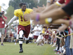 Photo - Washington Redskins quarterback Robert Griffin III (10) runs down a line of outstretched hands of fans during the afternoon practice at the NFL football teams training camp in Richmond, Va., Wednesday, July 31, 2013.   (AP Photo/Steve Helber)