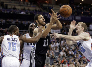 Photo - San Antonio Spurs' Jeff Ayres (11) is fouled as he drives between Charlotte Bobcats' Kemba Walker (15) and Cody Zeller (40) during the first half of an NBA basketball game in Charlotte, N.C., Saturday, Feb. 8, 2014. (AP Photo/Chuck Burton)