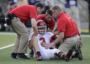Photo -   CORRECTS DAY OF WEEK - Utah quarterback Jordan Wynn (3) is helped off the field following a hit during the second quarter of an NCAA football game against Utah State on Friday, Sept. 7, 2012, in Logan, Utah. (AP Photo/Rick Bowmer)