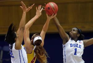 Photo - Duke's Elizabeth Williams blocks a shot by Winthrop's Schaquilla Nunn, also guarded by Duke's Oderah Chidom, during the first half of their first-round game in the NCAA basketball tournament in Durham, N.C., Saturday, March 22, 2014. (AP Photo/Ted Richardson)
