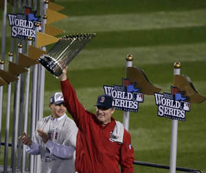 Photo - Boston Red Sox manager John Farrell holds up the championship trophy after Game 6 of baseball's World Series Wednesday, Oct. 30, 2013, in Boston. The Red Sox beat the St. Louis Cardinals 6-1 to win the series. (AP Photo/Chris Carlson)