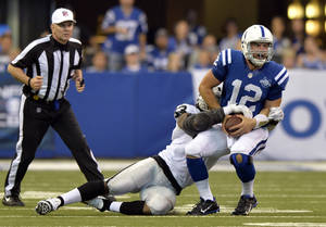 Photo - Indianapolis Colts quarterback Andrew Luck, right, is sacked by Oakland Raiders linebacker Jason Hunter during the second half of an NFL football game in Indianapolis, Sunday, Sept. 8, 2013. (AP Photo/Doug McSchooler)