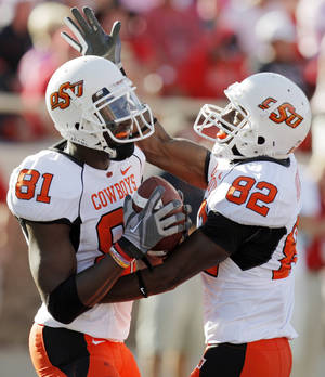 Photo - OSU's Justin Blackmon (81) and Isaiah Anderson (82) celebrate after a touchdown catch by Blackmon in the third quarter during the college football game between the Oklahoma State University Cowboys and Texas Tech University Red Raiders at Jones AT&T Stadium in Lubbock, Texas, Saturday, October 16, 2010. OSU won, 34-17. Photo by Nate Billings, The Oklahoman