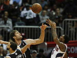 Photo - Brooklyn Nets center Brook Lopez (11) blocks a shot from Atlanta Hawks shooting guard Louis Williams (3) in the second half of an NBA basketball game on Wednesday, Jan. 16, 2013, in Atlanta. (AP Photo/John Bazemore)