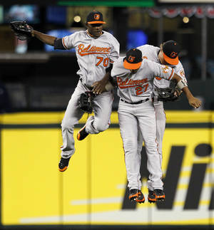 Photo -   Baltimore Orioles outfielders Xavier Avery (70), Endy Chavez (27) and Nate McLouth celebrate after defeating the Seattle Mariners in a baseball game Monday, Sept. 17, 2012, in Seattle. Baltimore won 10-4. (AP Photo/Elaine Thompson)