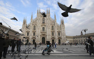 Photo - This Jan. 16, 2014 photo shows  visitors dodging birds in the piazza outside of Duomo cathedral in Milan, Italy. The ornate white facade of Milan's Duomo cathedral is the single most recognized symbol of the Lombard capital, taking centuries to complete.  (AP Photo/Antonio Calanni)