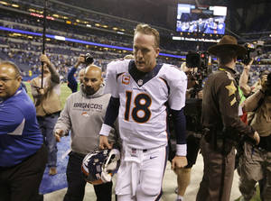 Photo - Denver Broncos quarterback Peyton Manning (18) walks off the field after  an NFL football game against the Indianapolis Colts, Sunday, Oct. 20, 2013, in Indianapolis. The Coltsd won 39-33. (AP Photo/Michael Conroy)