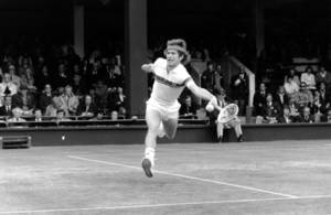 Photo - John McEnroe of the United States gets both feet off the ground as he leaps across Wimbledon's number one court to reach a shot from Bob Lutz, Friday, June 26, 1981.  McEnroe won the match 6-4, 6-2, 6-0.  (AP Photo/Peter Kemp)