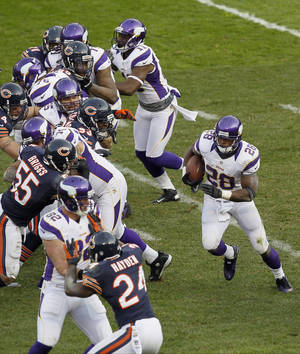 photo - Minnesota Vikings running back Adrian Peterson (28) looks for an opening against the Chicago Bears in the second half of an NFL football game in Chicago, Sunday, Nov. 25, 2012. (AP Photo/Charles Rex Arbogast)
