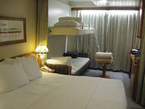 Photo - The staterooms in Disney Magic are cleverly designed and comfortable. The top bunk in the bakcground stows away in the ceiling and the bed below converts into a couch. <strong>DON MECOY - THE OKLAHOMAN</strong>