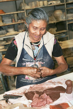 Photo - Guillermina Aguilar workis with clay to  make folk art chicken vases. PHOTO BY STEVE MAUPIN, FOR THE OKLAHOMAN    <strong>Copyright Steven N. Maupin</strong>