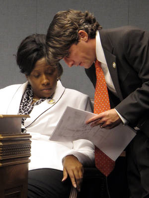 Photo - Rep. Katrina Jackson, D-Monroe, confers with Rep. Cameron Henry, R-Metairie, during the House Ways and Means Committee hearing on Monday, May 6, 2013, in Baton Rouge, La. Jackson and Henry are leaders involved in ongoing House budget negotiations that include bills advanced by the Ways and Means Committee. (AP Photo/Melinda Deslatte)