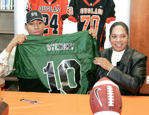Photo - Douglass' Destin Stewart, left, holds up a University of Hawaii jersey while his mother Sabena Watts looks on Feb. 4. PHOTO BY STEVE GOOCH, THE OKLAHOMAN