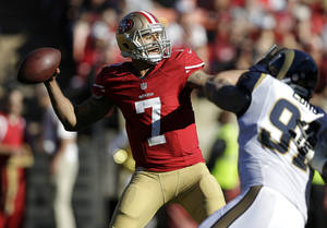 Photo - San Francisco 49ers quarterback Colin Kaepernick (7) passes as St. Louis Rams defensive end Chris Long (91) applies pressure during the second quarter of an NFL football game in San Francisco, Sunday, Dec. 1, 2013. (AP Photo/Marcio Jose Sanchez)
