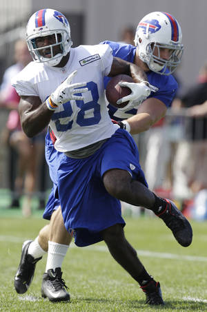 photo -   Buffalo Bills&#039; C. J. Spiller (28) runs under pressure from Tank Carder during NFL football training camp in Pittsford, N.Y., Friday, July 27, 2012. (AP Photo/David Duprey)  