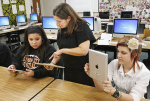 Photo - Teacher Melissa Rangel, center, works with seniors Marissa Santiago and Wheatley Crawley on iPads in the multimedia and image management class at Putnam City High School.  Photo BY  PAUL B. SOUTHERLAND,  THE OKLAHOMAN Archives