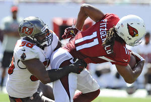 Photo - Tampa Bay Buccaneers linebacker Dekoda Watson (56) stops Arizona Cardinals wide receiver Larry Fitzgerald (11) after a reception during the third quarter of an NFL football game on Sunday, Sept. 29, 2013, in Tampa, Fla. (AP Photo/Brian Blanco)