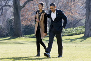 photo - President Barack Obama walks with daughter Malia on the first family's return from vacationing in Hawaii, on the South Lawn of the White House in Washington, Sunday, Jan. 6, 2013. (AP Photo/Jacquelyn Martin)